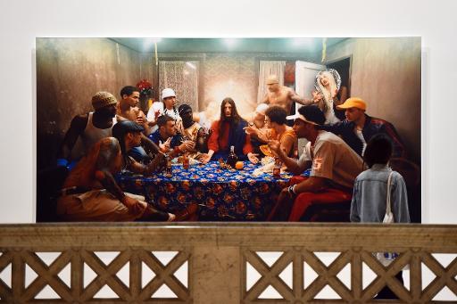"""Une femme devant des photos de David LaChapelle revisitant le dernier repas du Christ dans l'exposition """"Après le déluge"""" au Palazzo delle Esposizioni à Rome le 29 avril 2015 © GABRIEL BOUYS AFP"""