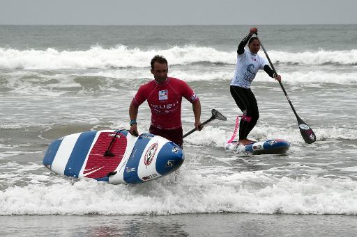 Eric Terrien (g) et Céline Guesdon, membres de l'équipe de France de stand up paddle, lors d'un entraînement sur la plage de Plouharnel dans le Morbihan, le 4 mai 2015 © Damien Meyer AFP/Archives