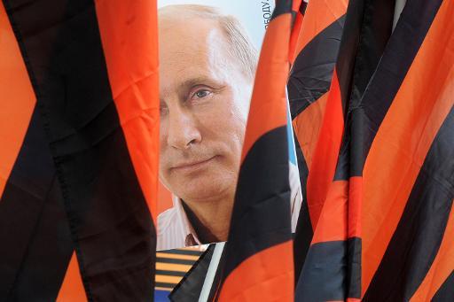 Un manifestant porte un portrait du président russe Vladimir Poutine encadré par deux drapeaux arborant le ruban de Saint Georges durant un rassemblement du 1er mai à Saint-Pétersbourg, le 1er mai 2015 © OLGA MALTSEVA AFP/Archives
