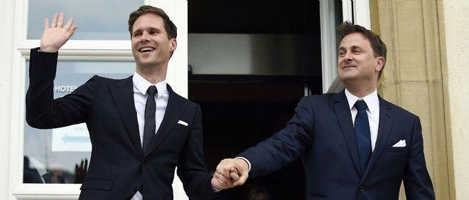 Le Premier ministre luxembourgeois Xavier Bettel (à droite sur la photo) et son mari Gauthier Destenay (à gauche), tous deux en costumes sombres, sont arrivés en marchant, la main dans la main.