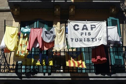"""Un balcon dans la banlieue de Barcelone auquel est accroché une banderole: """"pas d'appartements pour touristes"""" à Barcelone le 28 juin 2015 © QUIQUE GARCIA AFP"""