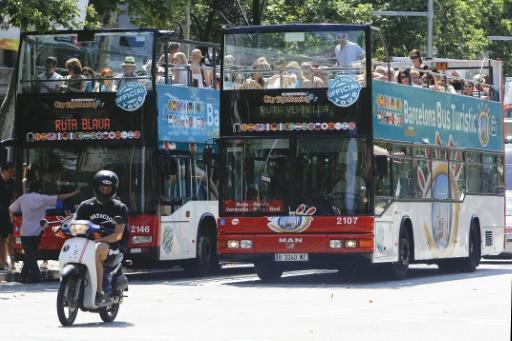 Des touristes participent à un tour de la ville en bus à Barcelone le 28 juin 2015 © QUIQUE GARCIA AFP