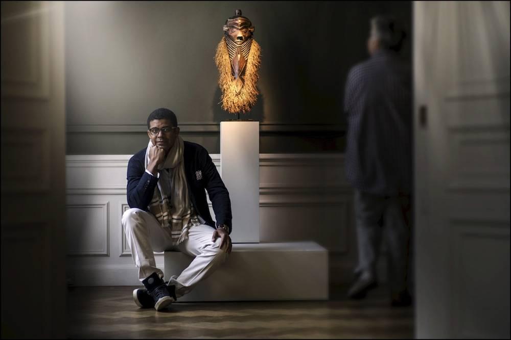 """Sindika Dokolo devant un masque pende de sa collection, l'une des plus importantes sur l'art contemporain africain, à l'exposition """"Uruzi Wa Dunia"""" (""""Beauté des mondes"""" en swahili) à Bruxelles en juin 2015. ©  DR"""