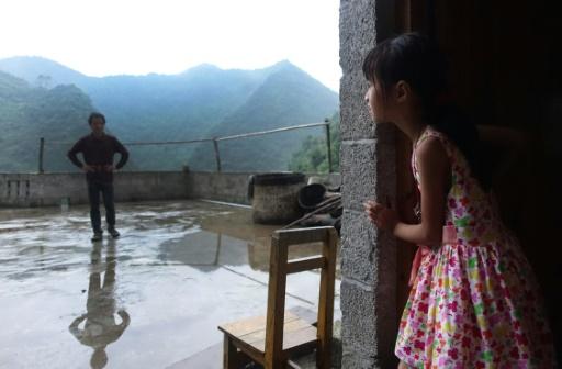 Meng Yiping, qui vit avec ses grands parents, parle avec son oncle dans sa maison à Longfu, dans la région autonome du Guangxi, le 19 juin 2015 © JOHANNES EISELE AFP