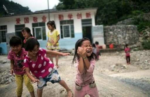 Des enfants jouent dans la cour d'une école primaire de Longfu Township, dans la région autonome de Guangxi en Chine, le 19 juin 2015 © JOHANNES EISELE AFP