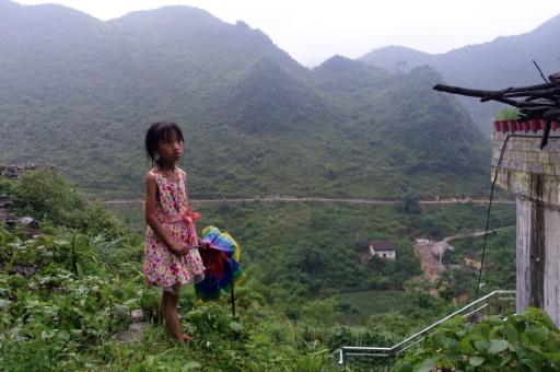 Meng Yiping, qui vit avec ses grands parents, pose près de sa maison à Longfu Township, dans la région autonome du Guangxi en Chine, le 19 juin 2015 © JOHANNES EISELE AFP
