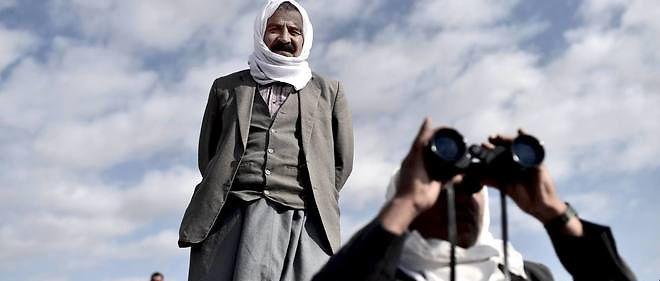 """Deux Kurdes scrutent à l'aide de jumelles la ville syrienne de Ain al-Arab (""""Kobane"""" pour les Kurdes), depuis la frontière, le 15 octobre dernier."""