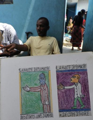 Les fils de l'artiste ivoirien Frédéric Bruly Bouabré montrent un manuscrit rempli de dessins de leur père dans la maison familiale d'Abidjan, le 30 juin 2014, au lendemain de sa mort © Sia Kambou AFP/Archives