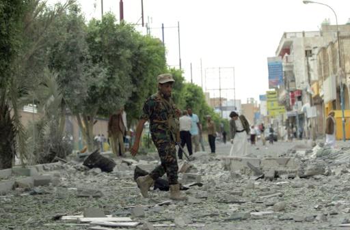 Un rebelle Houthi marche au milieu d'immeubles détruits après des frappes de la coalition arabe, le 5 septembre 2015 à Sanaa © MOHAMMED HUWAIS AFP