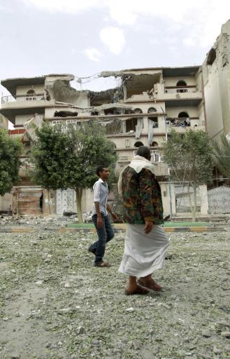 Des Yéménites marchent au milieu d'immeubles détruits après des frappes de la coalition arabe, le 5 septembre 2015 à Sanaa © MOHAMMED HUWAIS AFP