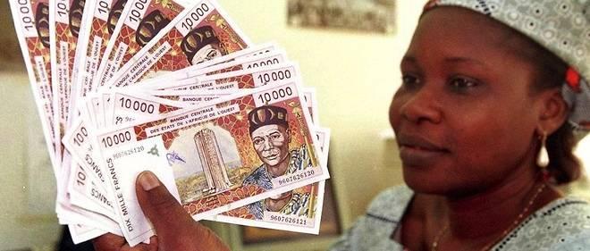 Une femme tient dans ses mains des billets de 10 000 francs. Ceux-ci sont émis par la BCEAO pour les pays ouest-africains membres de la zone CFA. La BEAC se charge elle de l'émission des billets pour les pays d'Afrique centrale membres de ladite zone.
