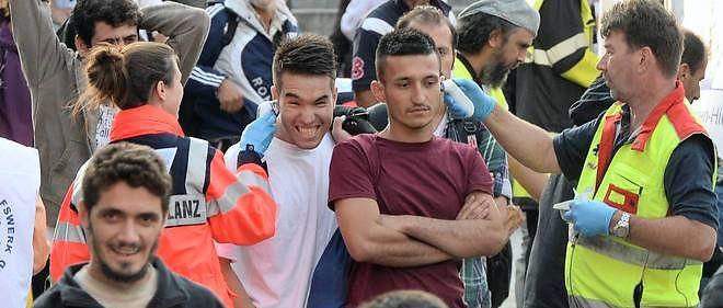 Des bénévoles accueillent les migrants venant de la Hongrie et d'Autriche le 5 septembre 2015 à la gare de Munich, en Allemagne.