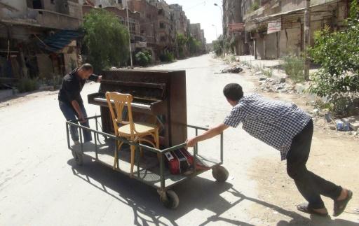 Image du 26 juin 2014 d'Aeham al-Ahmad, poussant son piano à Yarmouk, aux portes de Damas © RAMI AL-SAYED AFP/Archives