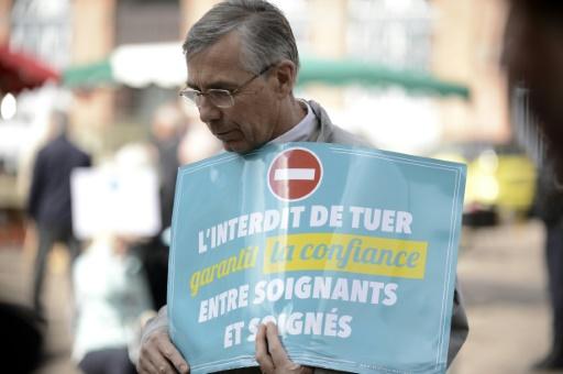 Un homme brandit une pancarte du collectif anti-euthanasie 'Soulager mais pas tuer', lors d'une manifestation devant la préfecture de Toulouse, le 3 octobre 2015 © Rémy GABALDA AFP