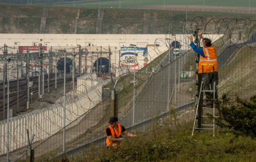 Des ouvriers réparent la clôture sécurisant l'Eurotunnel à Coquelles près de Calais le 3 octobre 2015 © PHILIPPE HUGUEN AFP