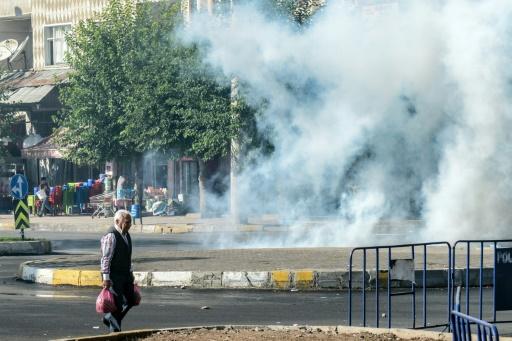 Un homme marche à côté de gaz lacrymogène lancé par la police turque à Diyarbakir, dans le sud-est du pays, le 10 octobre 2015 © ILYAS AKENGIN AFP/Archives