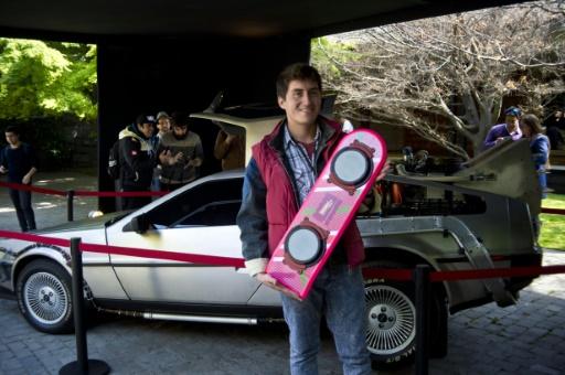 """Un fan pose avec une relique du skate volant de Marty McFly, devant la mythique DeLorean de la saga """"Retour vers le futur"""", à Santiago au Chili, le 21 octobre 2015 © MARTIN BERNETTI AFP"""