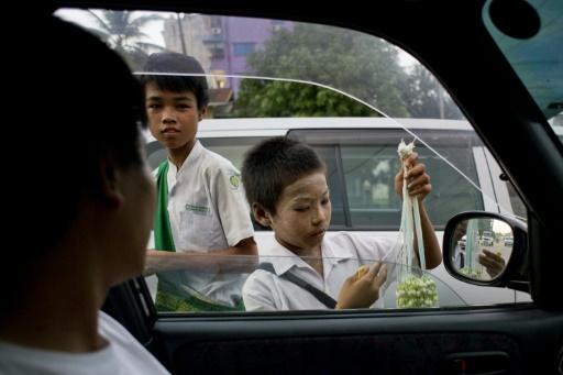 Des enfants vendent des fleurs dans la rue à Rangoun, le 20 octobre 2015 © Ye Aung Thu AFP