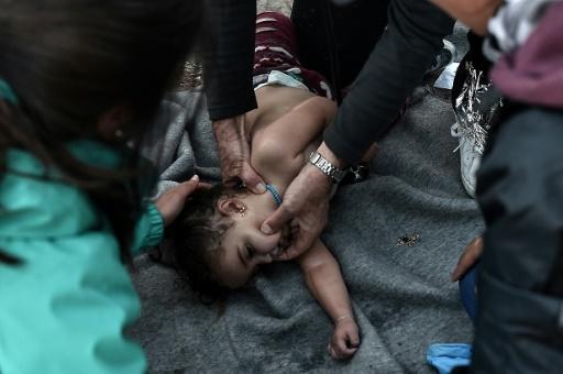 Des médecins tentent de réanimer un petit enfant après le naufrage d'un bateau de migrants le 28 octobre 2015 au large de l'île de Lesbos © ANGELOS TZORTZINIS AFP