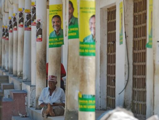 Un habitant installé sous des affiches de campagne, à Stone Town,  le centre historique de Zanzibar classé au patrimoine mondial de l'Unesco, le 27 octobre 2015 © Tony Karumba AFP/Archives