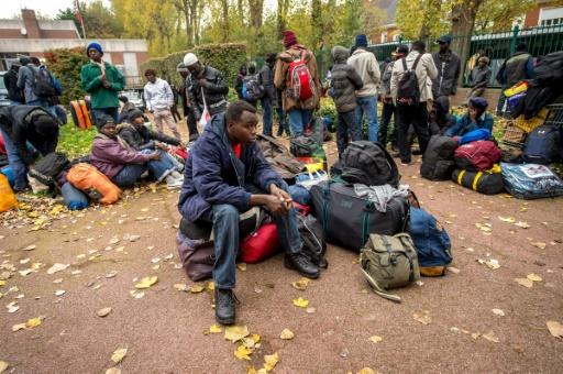 """Des migrants et des demandeurs d'asile, en grande majorité du Soudan, quittent le 27 octobre 2015 le campement de la """"jungle"""" à Calais pour rejoindre un """"centre d'accueil"""", éloigné des points de passage vers la Grande-Bretagne © PHILIPPE HUGUEN AFP"""