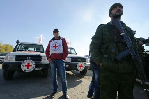 Des observateurs de la Croix-Rouge surveillent l'échange de prisonniers ukrainiens et prorusses à Chtchastia, dans l'est de l'Ukraine, le 29 octobre 2015 © ALEKSEY FILIPPOV AFP