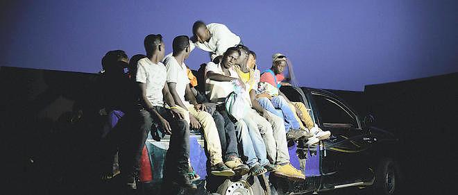 """Agadez est un carreffour commercial et migratoire dans le Sahel.  En partance pour l'Algérie ou la Libye pour rallier l'Europe, des milliers de migrants venant pricipalement d'Afrique de l'Ouest convergent chaque mois vers Agadez. Dans la cour d'un """"foyer"""" sénégalais, en vue d'un départ imminent vers la Libye, des migrants ont pris place sur le pick-up qui leur fera traverser le désert."""
