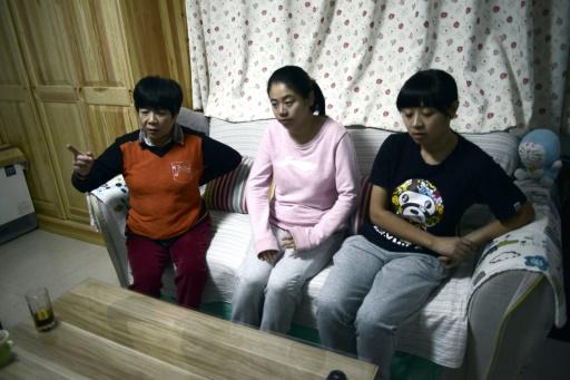 Li Xue chez elle à Pékin, le 31 octobre 2015, avec sa soeur Li Bin (d) et sa mère Bai Xiuling (g) © GOH CHAI HIN AFP