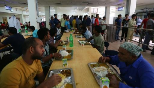 """Des travailleurs étrangers prennent un repas à la cafétéria de la """"Labour City"""", le 3 mai 2015 à Doha, une cité-dortoir destinée à héberger près de 70.000 travailleurs étrangers en vue du Mondial-2022 de football au Qatar © Marwan Naamani AFP"""