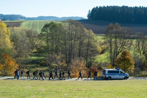 Des migrants et réfugiés suivent un véhicule de police après avoir traversé la frontière avec l'Autriche, le 1er novembre 2015 près de Wegscheid, dans le sud de l'Allemagne © Sebastian Kahnert DPA/AFP