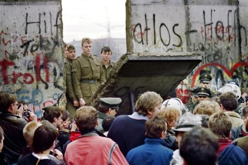 Des Allemands de l'Ouest à Berlin le 11 novembre derrière le mur alors que des gardes-frontières est-allemands détruisent une portion du mur © Gerard Malie AFP