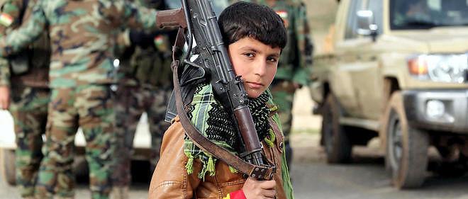 Un yézidi de 10 ans accompagne des peshmergas dans les montagnes du Sinjar.