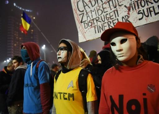 Des manifestants expriment leur colère contre la classe politique roumaine, le 7 novembre 2015 à Bucarest, habillés aux couleurs du drapeau national © DANIEL MIHAILESCU AFP