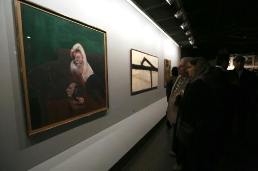 """Des visiteurs devant le tableau de Francis Bacon """"Reclining Man with Sculpture"""" au musée d'art contemporain de Téhéran en Iran, le 20 novembre 2015 © ATTA KENARE AFP"""