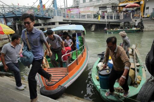 Des touristes reviennent d'un tour en bateau pour voir les dauphins roses, à Tai O, à Hong Kong, le 4 novembre 2015 © Isaac Lawrence AFP