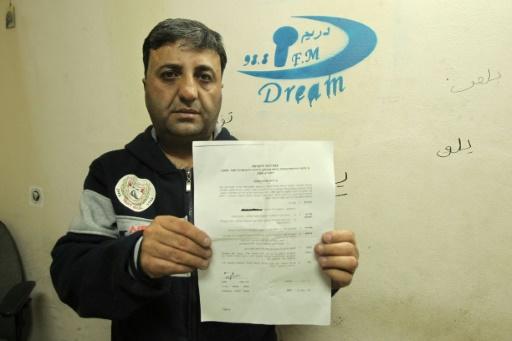 """Le propriétaire de la station de radio """"Dream"""", Talab Jaabari, montre l'ordre de fermeture pour six mois de cette troisième radio d'Hébron, le 29 novembre 2015 © HAZEM BADER AFP"""