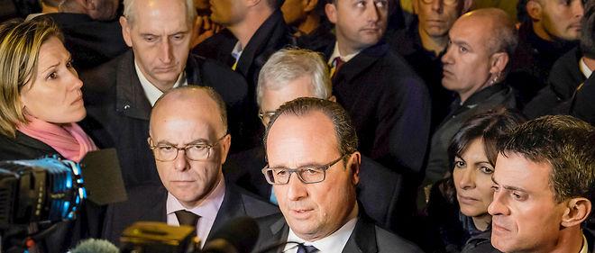 """Le chef de l'État devant le Bataclan – entouré de Bernard Cazeneuve, d'Anne Hidalgo et de Manuel Valls –, dans la nuit du 29 au 30 novembre. """"Nous voulions être là, parmi ceux qui ont vu ces choses atroces, pour dire que nous allons mener le combat et qu'il sera impitoyable"""", a-t-il déclaré."""