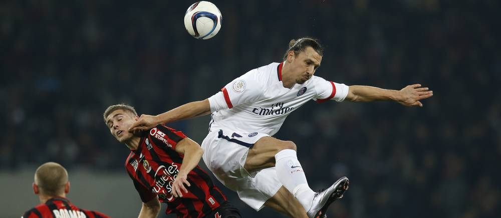"""Paris Saint-Germain's Swedish forward Zlatan Ibrahimovic (R) and Nice's French defender Maxime Le Marchand go for a header during the French L1 football match Nice (OGC Nice) vs Paris Saint-Germain (PSG) on December 4, 2015 at the """"Allianz Riviera"""" stadium in Nice, southeastern France.  AFP PHOTO / VALERY HACHE / AFP / VALERY HACHE"""