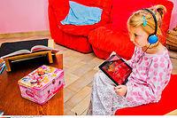 Une petite fille de 6 ans écoutant de la musique avec un casque  et une tablette. ©GILE MICHEL