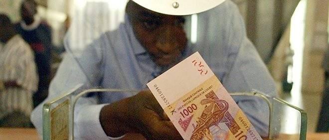 Un homme au guichet d'une banque, on lui tend un billet de 1 000 francs CFA, de la Banque centrale des Etats d'Afrique de l'Ouest (BCEAO).