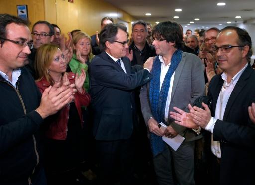 L'indépendantiste catalan Artur Mas  (g)félicite le nouveau candidat à la présidence de la région, Carles Puigdemont (d), le 9 janvier 2016 à Barcelone © LLUIS GENE AFP