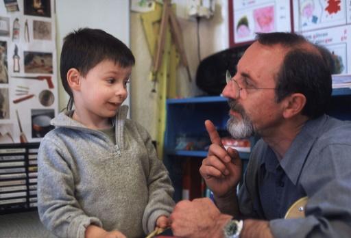 """Photo datée du 28 août 2002 montrant l'instituteur Georges Lopez (d) et Jojo durant le tournage du documentaire français """"Etre et avoir"""" de Nicolas Philibert ©  AFP/Archives"""