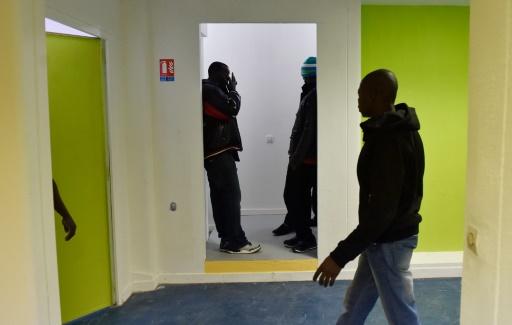Des migrants se tiennent dans l'ancien lycée Jean-Quarré, transformé en centre d'hébergement, le 5 février 2016 à Paris © ALAIN JOCARD AFP
