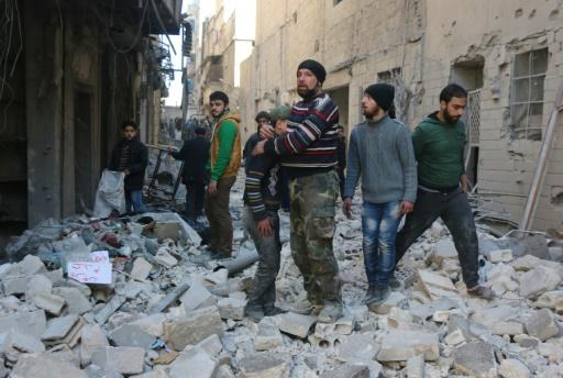 Des Syriens dans les décombres de bâtiments détruits par des frappes aériennes, le 4 février 2016 à Alep © THAER MOHAMMED AFP