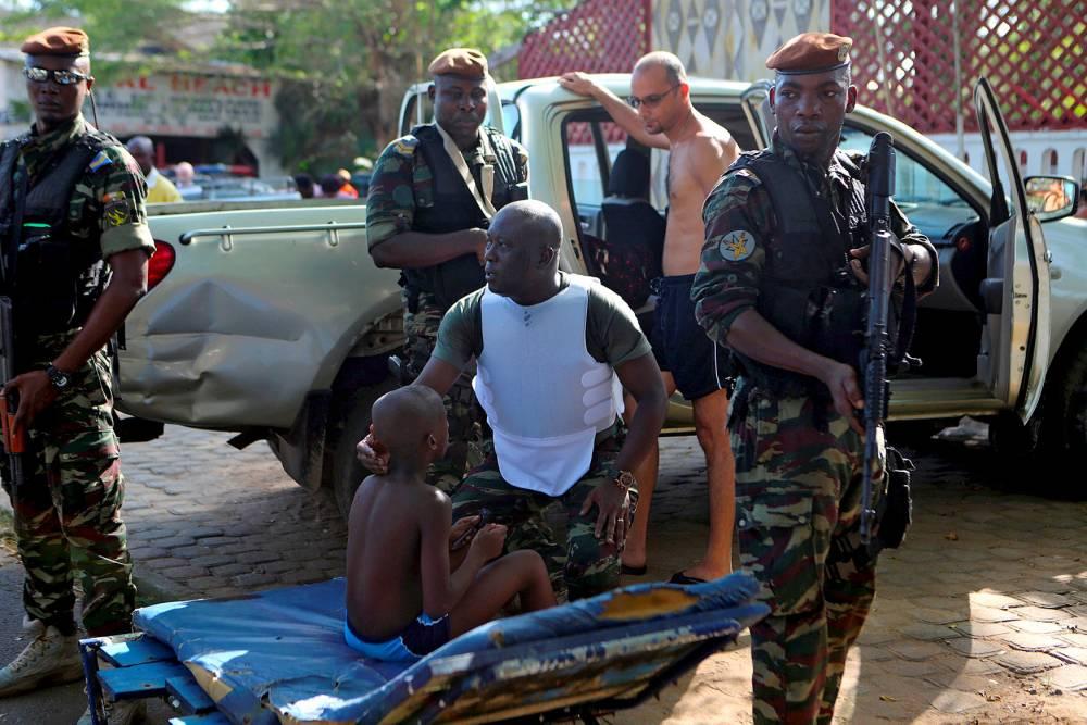 Un soldat réconforte un enfant blesséà Grand-Bassam (Côte d'Ivoire) le 13 mars ©  Joe Penney/Reuters