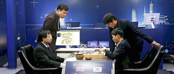 Face-à-face. Lee Sedol (assis à droite), champion du monde du jeu de go, affronte AlphaGo, dont les coups sont reportés sur le plateau par Aja Huang (assis à gauche). Ils disputent ici leur deuxième partie, le 10 mars, à Séoul.