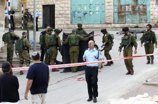 Des soldats israéliens couvrent le corps d'un assaillant palestinien tué par un soldat israélien à Hébron en Cisjordnaie occupée le 24 mars 2016 © HAZEM BADER AFP/Archives