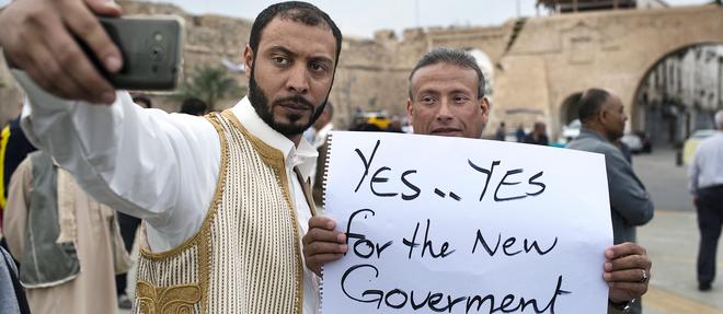 À Tripoli, en avril 2016, sur la place des Martyrs, lors d'un rassemblement, deux  manifestants se prennent en photo en affichant leur soutien au nouveau gouvernement. ©MICHAEL ZUMSTEIN / AGENCE VU'
