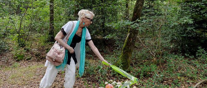 Une femme dépose une gerbe de fleurs à Monterfil.