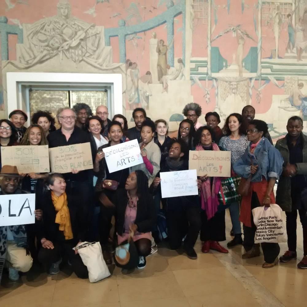 Les membres du collectif Décoloniser les Arts brandissent leurs pancartes de revendications. ©  Jalil Leclaire